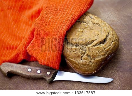 Fresh Bread Under A Napkin And Knife