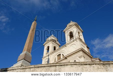 Twin belfries of Trinità dei Monti renaissance church with egyptian obelisk, seen from a side stairway