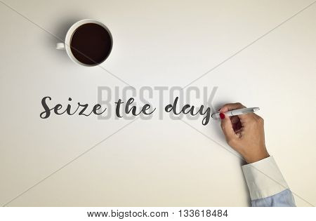 high-angle shot of a cup of coffee on an off-white surface and a young woman writing the text seize the day with a pen