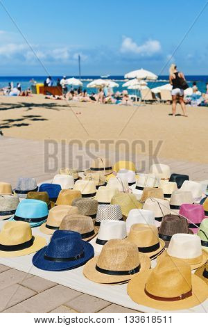 closeup of some different straw hats on sale at the seafront of La Barceloneta Beach in Barcelona, Spain