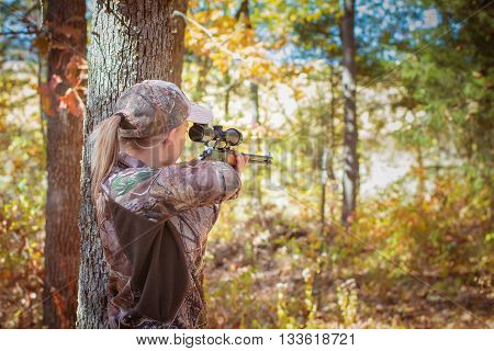 Woman holds a scoped rifle in the fall aiming next to a tree