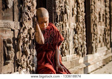 MANDALAY MYANMAR-FEB 3 2016 : Burmese novice sleeping in front of the old wood carving door at Shwenandaw Kyaung Temple Mandalay Myanmar