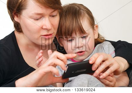 Mother and daughter indoors playing with smartphone
