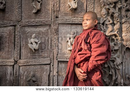 Burmese Novice, Young Monks, Standing In Front Of The Wood Carving Door
