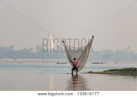 Unidentified asian fisherman catches fish with lift net traditional fishering tool at river on sunrise