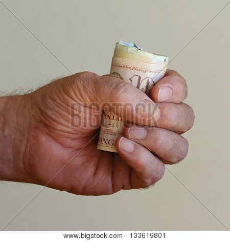 A fist full of valuable Singaporean dollars.