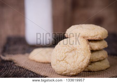 Sugar cookies stacked in front of a jar of milk
