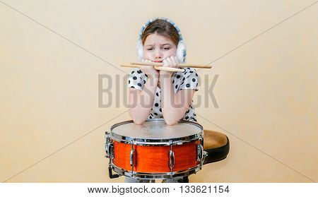 upset, bored little girl sitting and thinking behind the snare drum against Tuscan sun Venetian plaster wall background