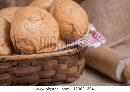 Dinner rolls in a basket up close with wood rolling pin in background