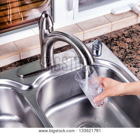 Hand holding drinking glass while being filled with tap water from kitchen faucet.