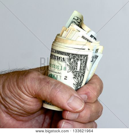 A offering of a fist full of American dollars.