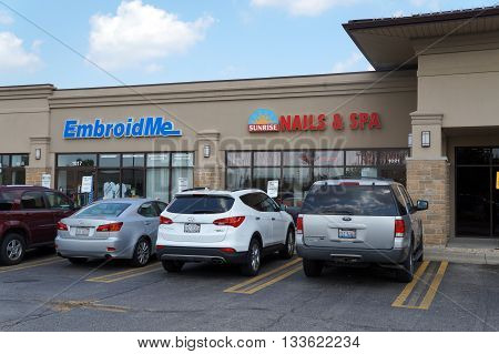 SHOREWOOD, ILLINOIS / UNITED STATES - AUGUST 16, 2015: One may have clothing embroidered at Embroid Me, and have one's nails trimmed at Sunrise Nails & Spa, in a Shorewood strip mall.