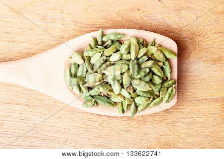 Green cardamom pods heap on wooden spoon rustic table background