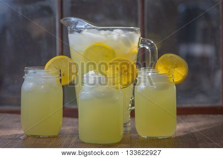 Lemonade in glass jars with pitcher and window in background