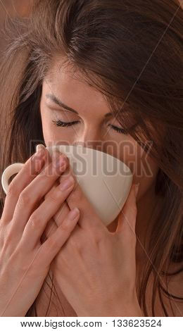 Beautiful latin woman drinking tea cup after relaxing beauty center treatment.
