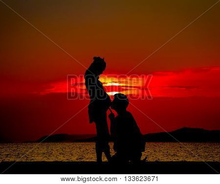father's Day : Silhouetted of Young father talk to son or daughter at the beach at the sunset time.