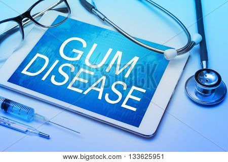 Gum disease word on tablet screen with medical equipment on background
