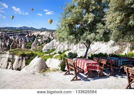 Restaurant in Goreme with view to tufa formations and hot air balloon in Cappadocia Turkey