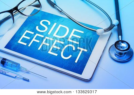 Side Effect word on tablet screen with medical equipment on background