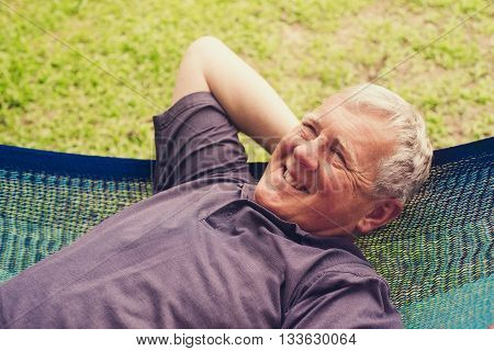 Older smiling man,relaxing in a hammock, selective focus,