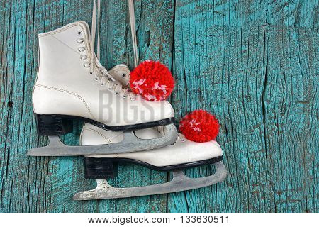 Pair of white ice skates with red and white yarn pompoms on turquoise painted rustic barn wood.