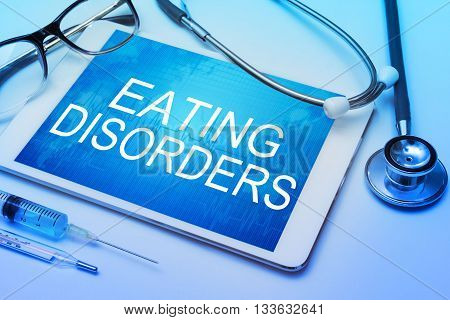 Eating disorder word on tablet screen with medical equipment on background