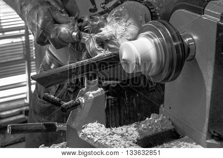 Black and white image of a craftsman working a piece of wood on a lathe