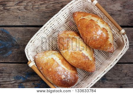 Three fresh French bread in a basket on a wooden platform top view. White bread fresh pastries loaf. Food.