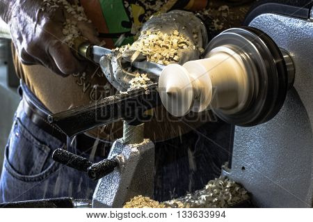 Close up of a craftsman turning a piece of wood on a lathe