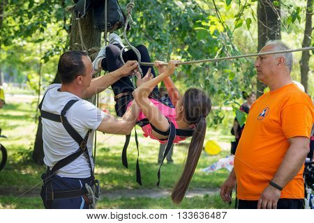 Zaporizhia/Ukraine- June 5, 2016: teen girl training on tyrolean traverse fixed on trees under adult volunteers supervision on charity family festival organized in regions with most quantity of refugees from Donetsk area, occasioned with International Chi