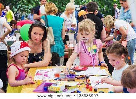 Zaporizhia/Ukraine- June 5, 2016: children with parents participating in drawing workshop on charity family festival organized in regions with most quantity of refugees from Donetsk area, occasioned with International Children`s Day