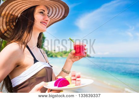 woman tourist at tropical beach eating fruit like water melon, pineapple and barbary fig for breakfast