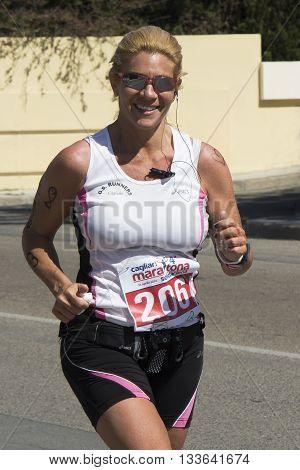 QUARTU S.E., ITALY - April 21, 2013: Fourth marathon of solidarity - Sardinia - portrait of a beautiful smiling woman running in city street