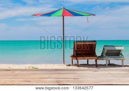Wood table top on Beautiful Turquoise sea and white sand beach with beach chairs and colorful umbrellaon beach in phuket Thailand summer holiday conceptsfor beautiful summer scenery background