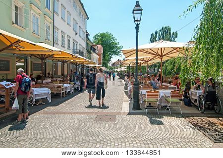 Ljubljana Slovenia - June 7 2016 People walking and sitting in cafe bars in Ljubljanas old town center on a bright sunny day
