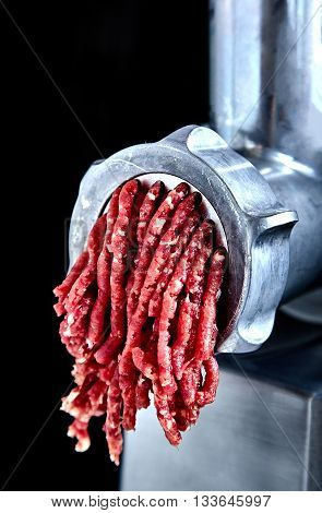 The process of transformation meat into forcemeat. Close up of front part of meat grinder or mincing-machine with ground beef exiting therefrom.