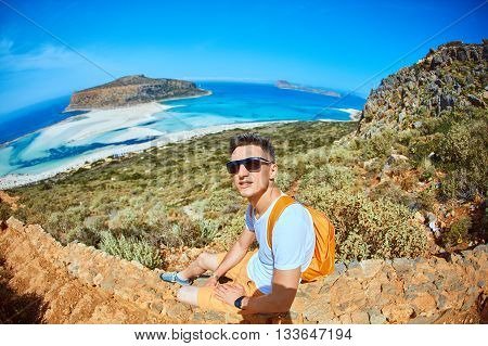 male traveler with backpack sitting on the trail against sea and blue sky at early morning. Balos beach at background