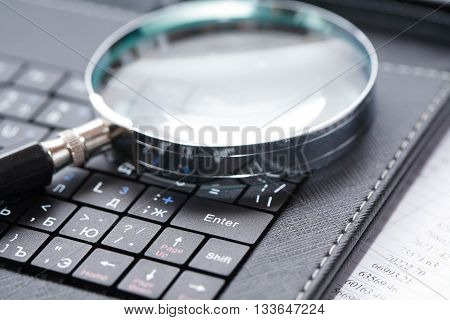 Business concept. Magnifying glass on black laptop keyboard