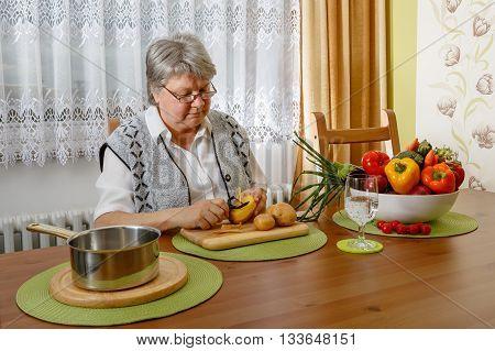 Senior Is Peeling Potatoes At A Table