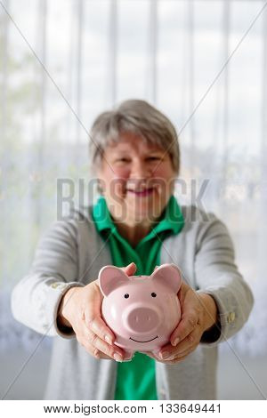 Laughing Senior offers her piggy bank .