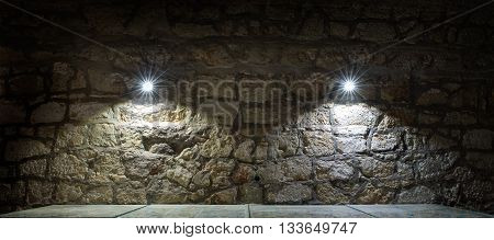 Stone wall and a table lighted two lamps