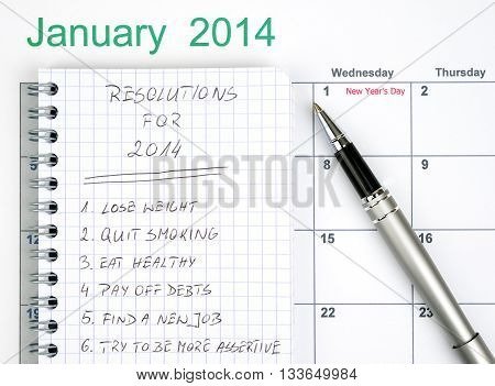 New Year's resolutions listed in the notepad with calendar and pen