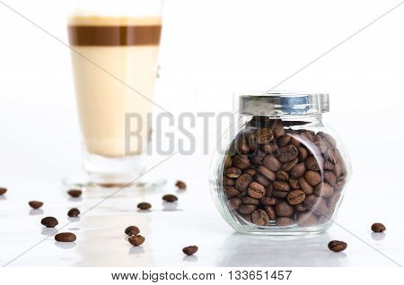 Transparent jar with coffee beans and latte macchiato isolated on white background