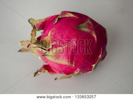 Exotic dragon fruit (Hylocereus monacanthus Pitahaya Pitaya) isolated on grey textured background. Bright red violet skinned fruit with violet flesh. Artistic retouching.