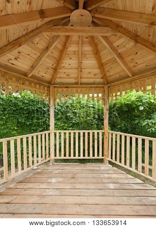 Inside of wooden gazebo in green garden under construction