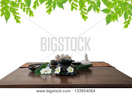 Thai spa massage setting herbal compress balls essential oil bottle frangipani and incense on green leaves background