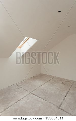 Attic room under construction with gypsum plaster boards and window