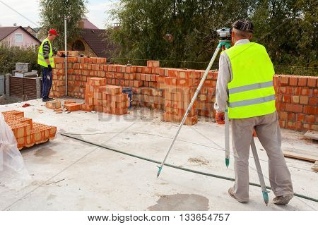 A worker with theodolite checks the validity of bricklaying