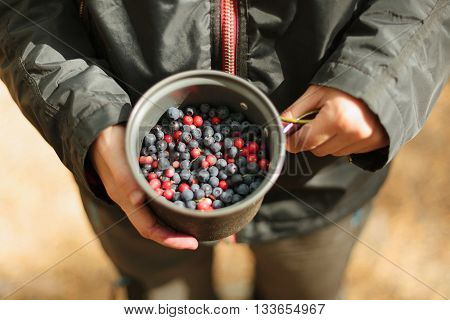A girl holding a pot of blueberries and cranberries in the wood