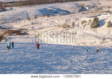 People skiing and snowboarding on the slopes of snow-covered hill.